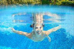 Child swims in pool underwater Stock Photos