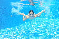 Child swims in pool underwater Stock Images