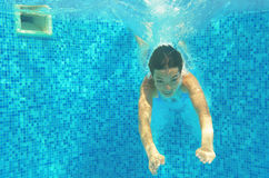 Child swims in pool underwater, happy active girl jumps, dives and has fun, kid sport. On family vacation Stock Images