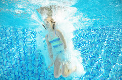 Child swims in pool underwater, happy active girl jumps, dives and has fun under water, kids fitness and sport Royalty Free Stock Images