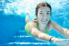 Child swims in swimming pool underwater, happy active teenager girl dives and has fun under water, kid fitness and sport. On family vacation on resort Stock Image