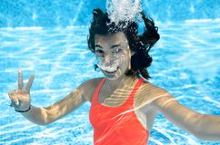Child swims in swimming pool underwater, happy active teenager girl dives and has fun under water, kid fitness and sport. On family vacation on resort Royalty Free Stock Photo