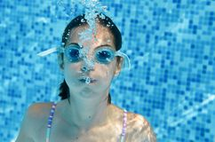 Child swims in swimming pool underwater, happy active teenager girl dives and has fun under water, kid fitness and sport. On family vacation on resort Stock Images