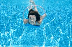 Child swims in swimming pool underwater, happy active teenager girl dives and has fun under water, kid fitness and sport. On family vacation on resort Stock Photo