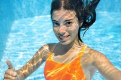 Child swims in swimming pool underwater, happy active teenager girl dives and has fun under water, kid fitness and sport. On family vacation on resort Royalty Free Stock Images