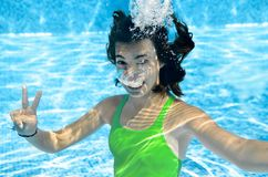 Child swims in swimming pool underwater, happy active teenager girl dives and has fun under water, kid fitness and sport. On family vacation on resort Royalty Free Stock Photography