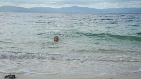 Child swims in the tropical sea stock video
