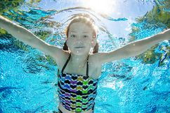Child swims underwater in swimming pool, happy active teenager girl dives and has fun under water, kid fitness and sport stock photos
