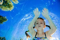 Child swims underwater in swimming pool, happy active teenager girl dives and has fun under water, kid fitness and sport royalty free stock image