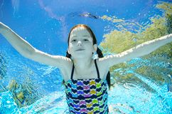 Child swims underwater in swimming pool, happy active teenager girl dives and has fun under water, kid fitness and sport royalty free stock images