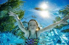 Child swims underwater in swimming pool, happy active teenager girl dives and has fun under water, kid fitness and sport royalty free stock photo