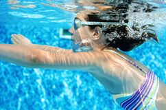 Child swims underwater in swimming pool, happy active teenager girl dives and has fun under water, kid fitness and sport stock photography