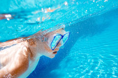 Child swims underwater in swimming pool Royalty Free Stock Photography