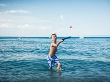 Child in swimware playing in sea Stock Photography