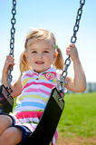 Child on swing. Young child on swing in playground outdoors stock image