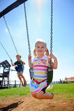 Child on swing. Young girl on swing in playground outdoors Stock Image