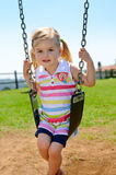 Child on swing. Young child on swing in playground outdoors stock images
