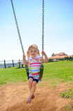 Child on swing. Young child on swing in playground outdoors royalty free stock image