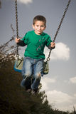 Child on swing. Smiling chilid,  boy with blue eyes on swing having fun Royalty Free Stock Photos