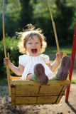 Child on swing. Laughing child on swing in summer park Stock Image