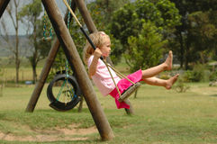 Child on swing. A beautiful little blond caucasian girl child sitting on the swing and swinging at the playground in the park