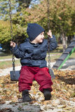Child on swing. A small child, boy, playing on a swing in a playground in the autumn or fall Stock Image