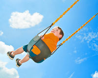 Child on swing. At playground under cloudy blue sky royalty free stock photography