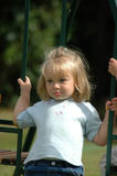 Child on swing. A beautiful little caucasian white girl child head portrait with sad expression in the face sitting on a swing, swinging and watching other kids Royalty Free Stock Image