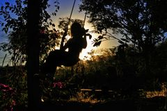 Child plays on swing at dusk stock photo