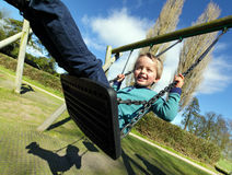 Child on a swing. Carefree child on a swing in a park on summer day stock photography