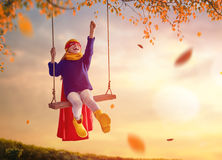Child on swing. Happy child on swing in sunset fall. Little kid playing in the autumn on the nature walk. Girl in superhero costume Stock Photography
