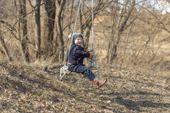 Child on a swing on nature in spring.  stock image