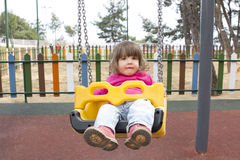 Child on swing in playground Stock Photos