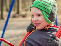 Child on Swing in spring time. The kid is having a great time out at the park playing on the swing. Smiling boy on playground swing Stock Photography