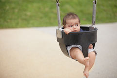 Child on a swing. Stock image of an infant on a swing. He does not look to happy Stock Images
