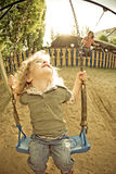 Child on swing in summer. Child on swing on playground Royalty Free Stock Photo