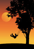 Child on swing in the sunset. Stock Images