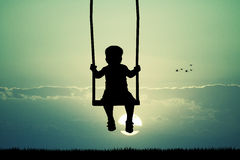 Child on swing at sunset Royalty Free Stock Photos