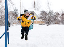Child on a swing in the winter. Happy child on a swing in the winter stock photos