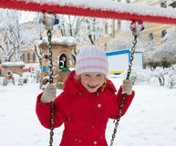 Child on swing in winter park Stock Image