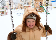 Child on swing in winter park Stock Photos