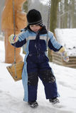 Child on swing at winter. Playground with snow stock image