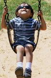 Child Swinging. In the park and enjoying the summer sun Stock Image