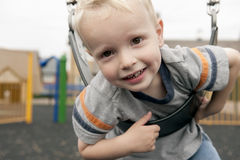 Child Swinging. Child on his tummy swinging at the playground.  Young boy is happy to be playing, with a big smile and play area in the background Stock Photo