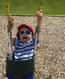 Child Swinging in Bucket Seat. Child Laughing and Swinging in Rubber Bucket Seat at the Playground on a sunny day Stock Photography