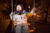 Child swinging at night Stock Photos