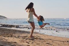 Child swinging parent beach stock photos