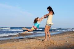 Child swinging parent beach Stock Image