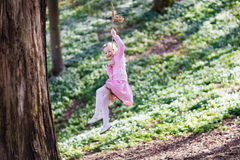 Child swinging on tree rope swing Stock Image