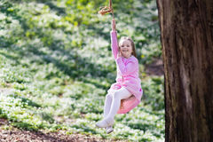 Child swinging on tree rope swing Royalty Free Stock Images